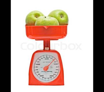 Red kitchen scale weighting nectarines